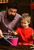 Ojciec i syn Ojca dzień Rodzinny dzień charcica Kwiat opieki podlewanie Glebowi użyźniacze szczęśliwe ogrodniczki z wiosną obrazy royalty free
