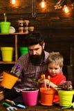 Ojciec i syn Ojca dzie? Kwiat opieki podlewanie Glebowi u?y?niacze Rodzinny dzie? charcica Brodaty m??czyzna i ch?opiec fotografia royalty free