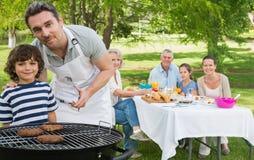 Ojciec i syn przy grilla grillem z rodzinnym mieć lunch w parku fotografia stock