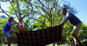 Ojciec i syn rozprzestrzenia pykniczną koc podczas gdy macierzysty niesie kosz 4k zdjęcie wideo