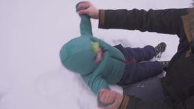 Ojciec i syn Troszkę kłama na śniegu chłopiec, i ojciec całuje on i łaskocze szczęśliwa rodzina Everyone jest zbiory wideo