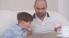 Ojciec i syn używa cyfrową pastylkę na kanapie w domu zdjęcie wideo