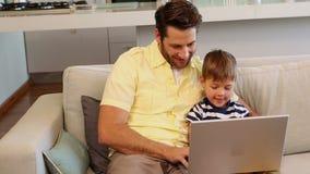Ojciec i syn używa laptop na kanapie zbiory