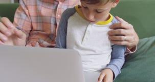 Ojciec i syn używa laptop na kanapie 4k w domu zbiory wideo
