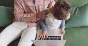 Ojciec i syn używa laptop na kanapie 4k w domu zdjęcie wideo