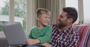 Ojciec i syn używa laptop na kanapie w wygodnym domu 4k zbiory wideo