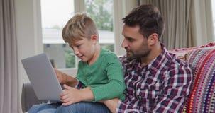 Ojciec i syn używa laptop w wygodnym domu 4k zbiory wideo