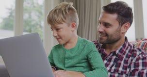 Ojciec i syn używa laptop w wygodnym domu 4k zdjęcie wideo