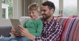 Ojciec i syn u?ywa cyfrow? pastylk? na kanapie 4k w domu zdjęcie wideo
