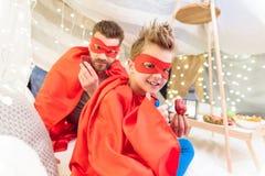 Ojciec i syn w bohaterów kostiumach je truskawki w powszechnym forcie Zdjęcie Stock