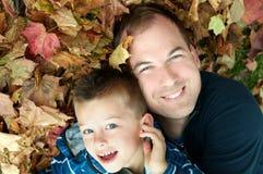 Ojciec i syn w liściach Zdjęcia Stock