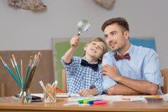 Ojciec i syn z magnifier Obrazy Royalty Free