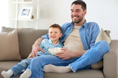 Ojciec i syn z popkornem ogląda tv w domu Obrazy Stock