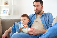 Ojciec i syn z popkornem ogląda tv w domu Zdjęcia Stock
