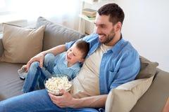 Ojciec i syn z popkornem ogląda tv w domu Fotografia Stock