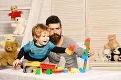 Ojciec i syn z rozochoconymi twarzami tworzymy kolorowego robot zdjęcie royalty free
