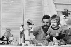 Ojciec i syn z szczęśliwymi twarzami tworzymy kolorowe budowy obrazy stock