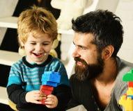 Ojciec i syn z szczęśliwymi twarzami tworzymy kolorowe budowy fotografia royalty free