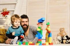Ojciec i syn z szczęśliwymi twarzami tworzymy kolorowe budowy obraz royalty free