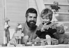 Ojciec i syn z uśmiechać się twarze tworzymy kolorowe budowy fotografia stock