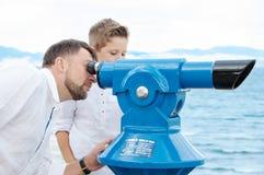 Ojciec i synowie przy morzem Rodzina na viewing platformie blisko monety zdjęcie royalty free