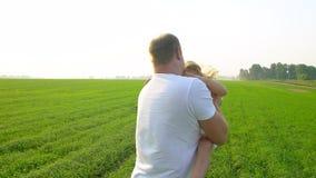 Ojciec i szczęśliwa dziecko dziewczyny córka na zmierzchu w zielonym polu Ojciec bawić się z małą córką Ściska ona zdjęcie wideo