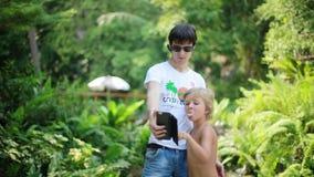 Ojciec jest ubranym okulary przeciwsłonecznych bierze obrazki z fotografii kamerą z jego synem przed siklawą Tajlandia Koh Samui zbiory