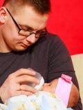 Ojciec karmi nowonarodzonej dziewczynki z dojną butelką Obrazy Stock