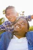 ojciec mieszał piggyback bawić się biegowego syna fotografia stock