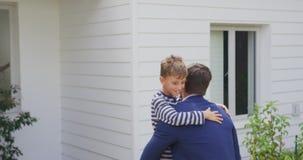 Ojciec niesie jego syna w domu ogródzie 4k zbiory