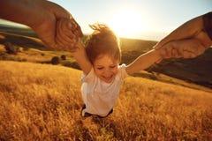 Ojciec obraca dziecka w polu w naturze zdjęcie stock