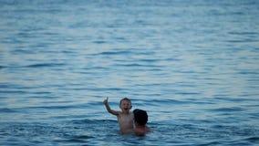 Ojciec podnosi up syna szczęśliwego dziecka z kciukiem up, silny i trustful, zwolnione tempo, zbiory
