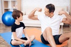 Ojciec pokazuje jego synowi jego mięśnie obrazy royalty free