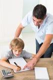 Ojciec pomaga chłopiec w rozwiązywać maths Zdjęcie Royalty Free