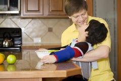 Ojciec pomaga niepełnosprawnego syna target706_0_ w kuchni Zdjęcia Stock