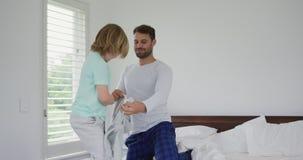 Ojciec pomocy syna być ubranym odziewa na łóżku w sypialni przy wygodnym domem 4k zdjęcie wideo