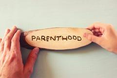 Ojciec ręka i dziecko ręki mienia znak z słowa rodzicielstwem, fotografia royalty free