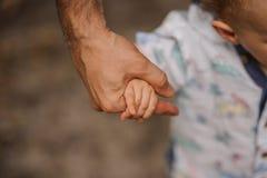 Ojciec ręki prowadzenie jego dziecko syn w lato lasowej naturze plenerowej, zdjęcia royalty free