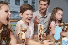 Ojciec Robi lodów Sundaes Z dziećmi W Domu zdjęcia stock