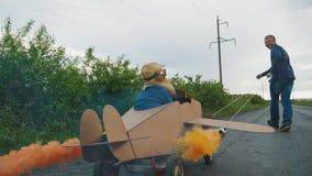 Ojciec stacza się jego syna na domowej roboty kartonu samolocie zbiory