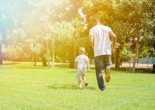 Ojciec, syna cyzelatorstwo i bieg i each inny w zieleń parku obrazy stock