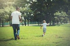 Ojciec, syna cyzelatorstwo i bieg i each inny w zieleń parku obraz royalty free