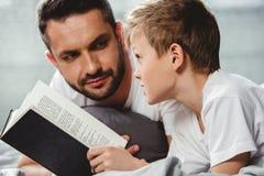 ojciec syna do czytania książki Obrazy Royalty Free