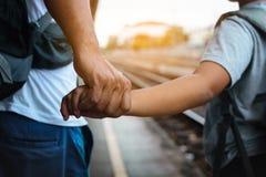 Ojciec, syna mienie i plecak ręki przy dworcem w Tajlandia i Obrazy Royalty Free