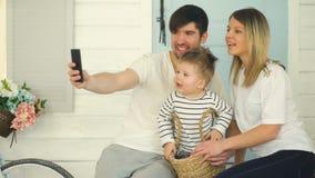 Ojciec szczęśliwa rodzina robi selfie z jego żoną wewnątrz stać na czele ich domowego drzwi małym synem i zbiory wideo