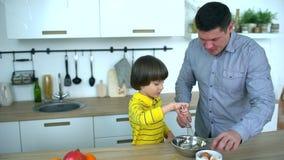 Ojciec trzepie jajka robić omelette Atrakcyjny ojciec i bardzo śliczna chłopiec robimy śniadaniu w kuchni Ojca ` s zdjęcie wideo