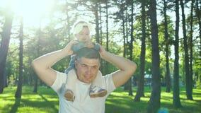 Ojciec trzyma jego dziewczynki na ramionach i klascze jej ręki z obiektywu racą zdjęcie wideo