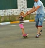 Ojciec uczy jego berbeć córki łyżwa obrazy royalty free