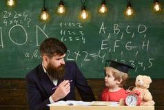Ojciec uczy syna, dyskutuje, wyjaśnia, jest edukacja starego odizolowane pojęcia Dzieciaka studiowanie z nauczycielem Nauczyciel  zdjęcia royalty free