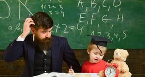 Ojciec uczy syna, dyskutuje, wyjaśnia, Nauczyciel w formalnej odzieży i uczniu w mortarboard w sala lekcyjnej, chalkboard dalej zdjęcie stock